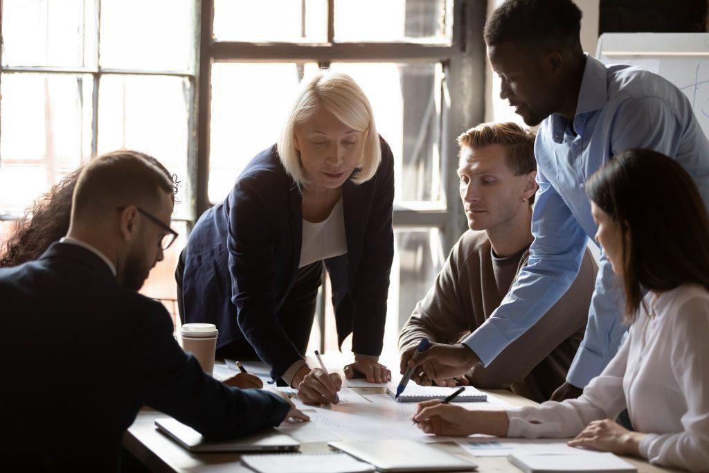 Older leader help diverse team in paperwork analysis at briefing