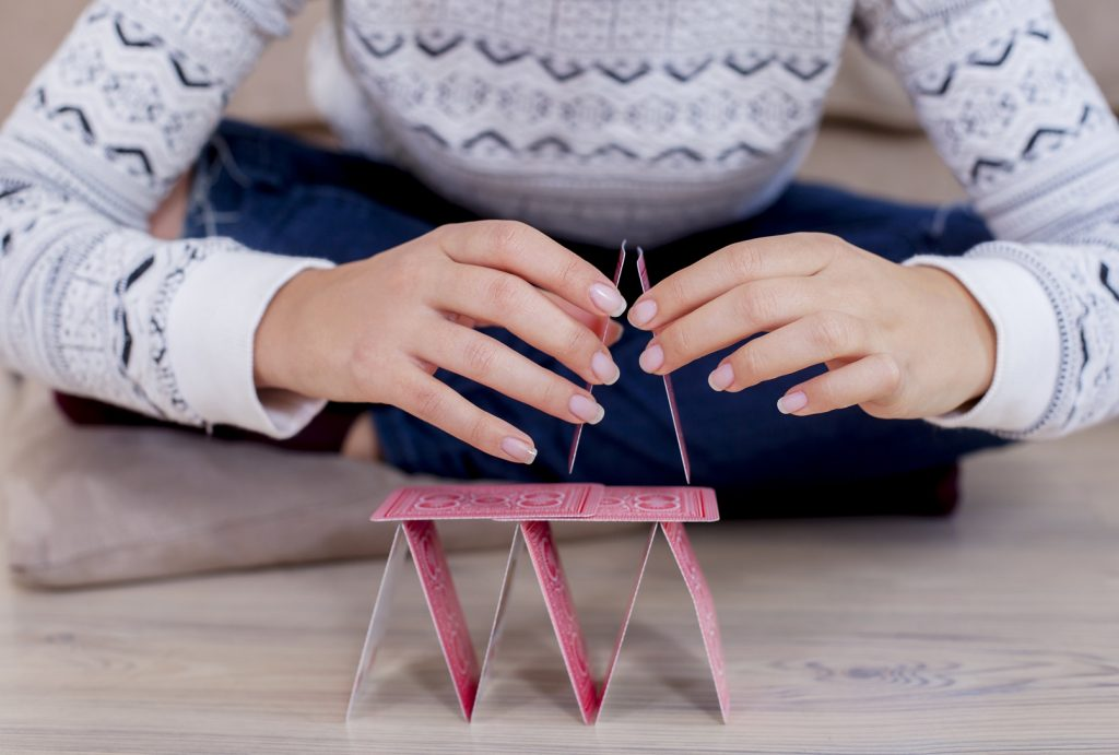 Womans hand building a house out of cards